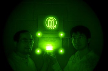 Zhengwei Pan, associate professor of physics and engineering, and postdoctoral researcher Feng Liu stand in a darkened room with infrared ceramic disks