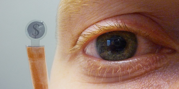 Contact lens displaying sign of dollar near human eye (Credit: IMEC)