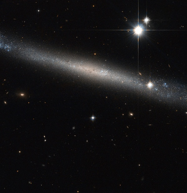 Thin Galaxy, IC 2233, with two bright stars in the upper right
