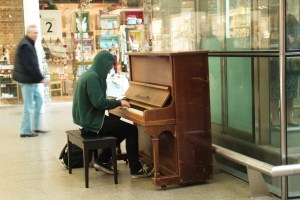 Young man playing piano at King's Cross St Pancras Underground Station