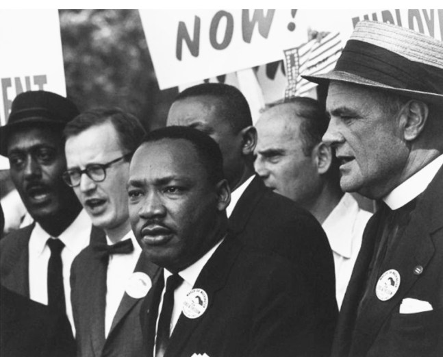 Dr. Martin Luther King Jr. is surrounded by Black and White people during the Poor People's Movement.