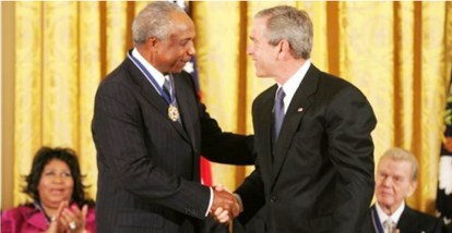 """President George W. Bush presents the Presidential Medal of Freedom to baseball legend Frank Robinson in the East Room Wednesday, Nov. 9, 2005. Winning the Most Valuable Player awards in the National and American Leagues, he achieved the American League Triple Crown in 1966. Mr. Robinson became baseball's first African-American manager. (Source: White House News & Policies / Wikimedia Commons) The citation reads: """"Frank Robinson played the game of baseball with total integrity and steadfast determination. He won Most Valuable Player awards in both the National and American Leagues. He achieved the American League Triple Crown in 1966. His teams won five League titles and two World Series championships. In 1975, Frank Robinson broke the color barrier as baseball's first African-American manager, and he later won Manager of the Year awards in both the National and American Leagues. The United States honors Frank Robinson for his extraordinary achievements as a baseball player and manager and for setting a lasting example of character in athletics."""""""
