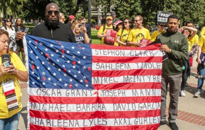 Malaki Seku Amen president of the California Urban Partnership with Khalil Ferguson at a rally at the State Capitol hold a flag with names of victims who were unarmed and killed by law enforcement. Photo by Russell Stiger Jr.