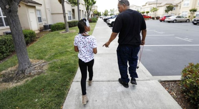 Maurice Caldwell walks with his daughter Amaya Haynes, 9, in Sacramento. (Francine Orr / Los Angeles Times)