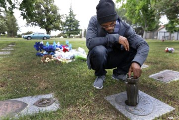 Zavion Johnson visits his daughter's grave in Sacramento. Johnson was convicted of second-degree murder in the 2001 death of his 4-month-old daughter, Nadia Dyvine Johnson. He was exonerated in 2017 and released from prison after 16 years. (Francine Orr / Los Angeles Times)
