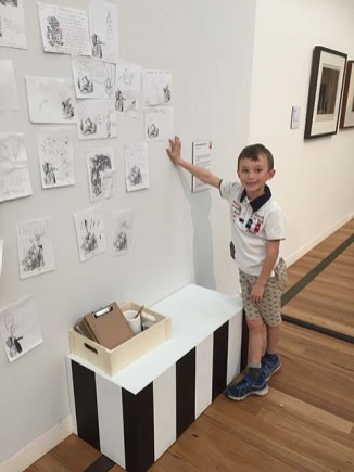 Samuel placing his work on the wall-r