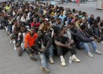Migrants rest after disembarking at the Sicilian port of Catania after being rescued at sea on 8