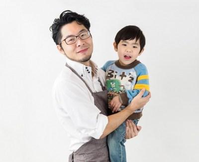 子どもを抱っこするエプロン姿の父親
