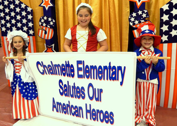 """Students, from left, Layla Serpas, Kylee Schallenberg and Nathan Schallenberg prepare to lead a procession with a sign singalling the theme of the Mardi Gras ball: """"Chalmette Elementary Salutes Our American Heroes.''"""