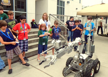 Junior Deputy Academy participants stand to examine the department's bomb robot, used to check suspicious items.