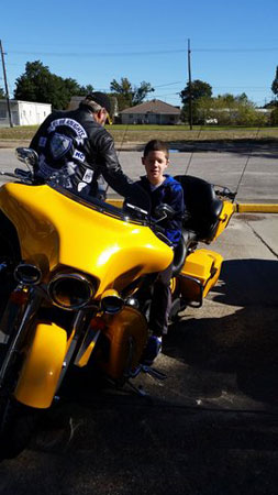 Brogan Burns, 12, sits at atop a motorcycle as Karl Melancon, retired Captain with the St. James Parish Sheriff's Office, speaks with him.