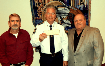 Sheriff James Pohlmann holds one of the checks given to the department by labor unions to purchase body armor for officers. At left is Al Bostick of the International Brotherhood of Electrical Workers and at right is Roy Serpas Jr. of the International Union of Operating Engineers.