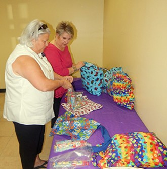 Shirley Pechon and Judy Hoffmeister check bags to be donated to the Sheriff's Office to give to children.