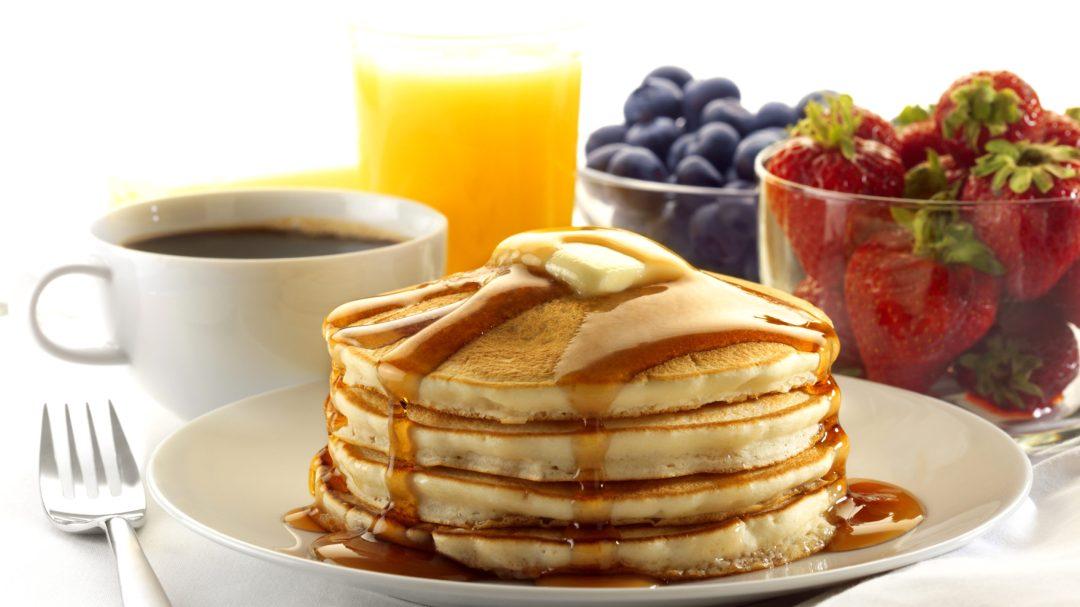 Stack of pancakes, coffee, strawberries, blueberries and orange juice