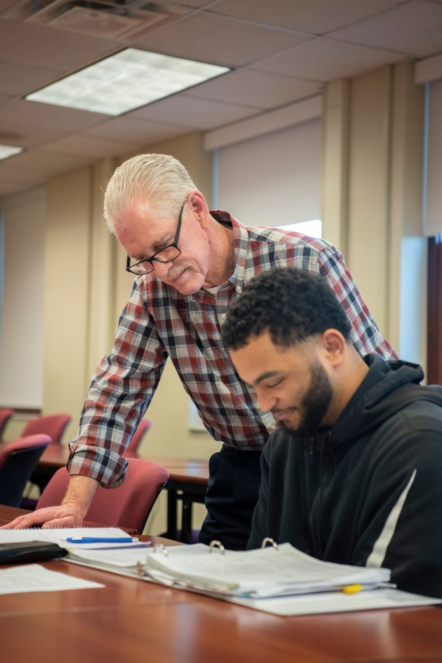 Male professor helps male student in accounting class.