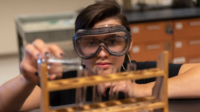 Female chemistry student does experiment with test tubes