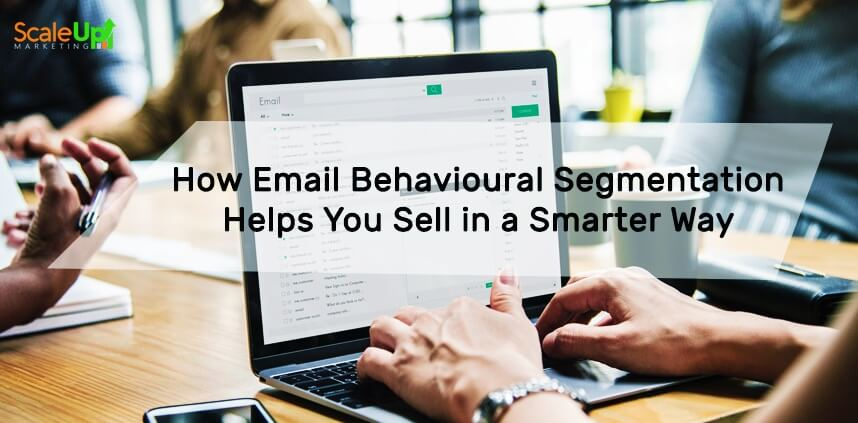 "header image of the blog title ""How Email Behavioural Segmentation Helps You Sell in a Smarter Way"" with an over-the-shoulder shot of a person typing on a laptop and a background of people sitting in front a wooden table"