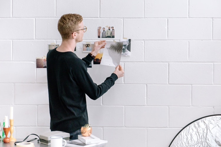 a man wearing black sweatshirt sticking papers on a white wall, this is an example of deciding and prioritizing for customer retention