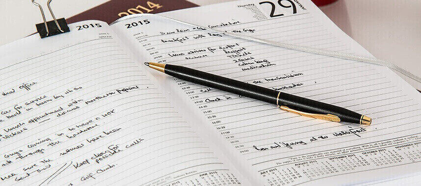 close up shot of a lying black pen above an open notebook