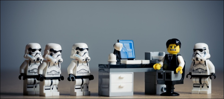 miniature of a worried business man sitting in front of his personal computer with 4 robots indicating that crm software should be opt for customization