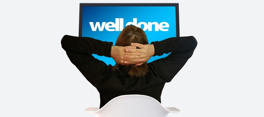 "a woman on her back resting her hand behind his head while looking to a screen with a message ""well done"""