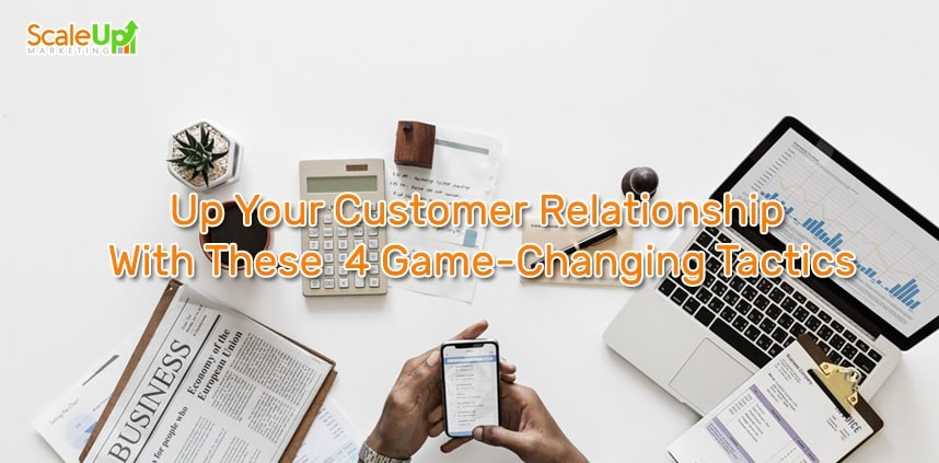 "header image of the blog title ""Up Your Customer Relationship With These 4 Game-Changing Tactics"" with an overhead shot of a hand holding a cellphone, a laptop, newspaper, calculator and a cactus around a white surface"