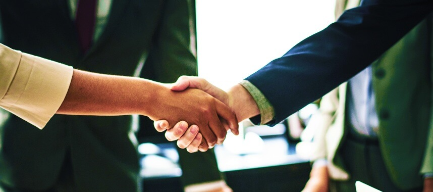 two shaking hands with a torso of a man wearing corporate attire