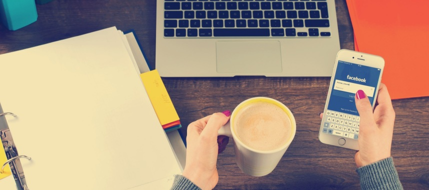 both hands holding a cup of coffee and a mobile phone with a laptop and folders placed on a wooden table, this is an example of social media sites to improve repeat purchase