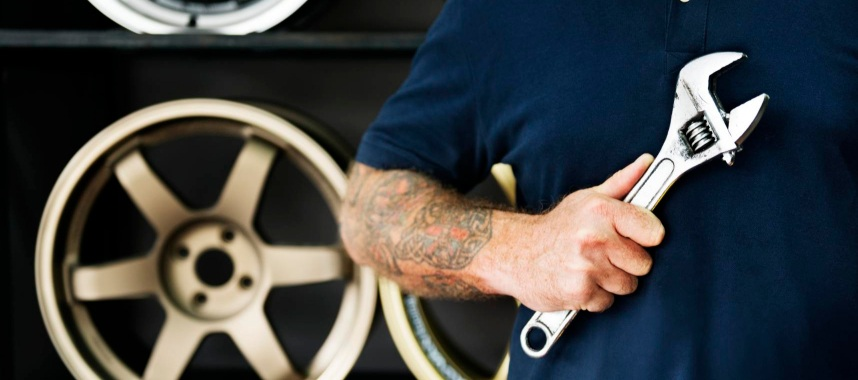 torso of a man wearing blue shirt holding a hand tool with a background of car rims displayed