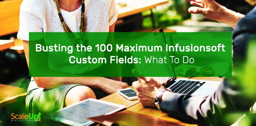 "header image of the blog title ""Busting the 100 Maximum Infusionsoft Custom Fields: What To Do"" with a background of 2 person talking with a cellphone, tablet and a laptop on top of a wooden table"