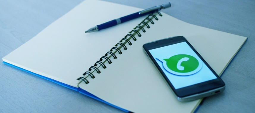 an open cellphone with a logo of whatsapp on a notebook and blue pen placed on a blue surface, whatsapp is one of the social media sites to get repeat purchase