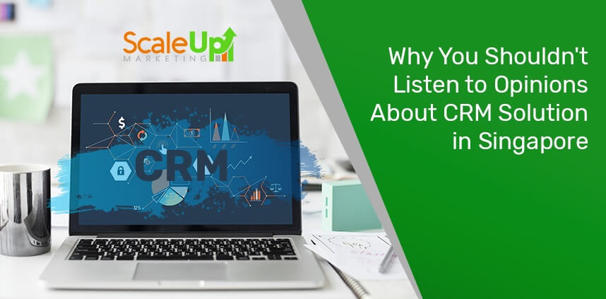 "header image of the blog title ""Why You Shouldn't Listen to Opinions About CRM Solution in Singapore"" with an open laptop with a word ""CRM"" on its screen and a stainless glass beside it with papers on a white surface"
