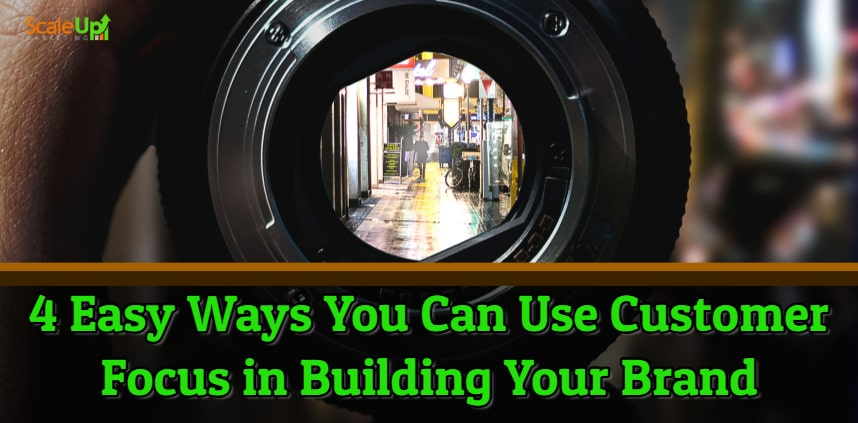 "blog title ""4 Easy Ways You Can Use Customer Focus in Building Your Brand"" with a left hand holding a camera lens focused to a wet street with a person walking straight"