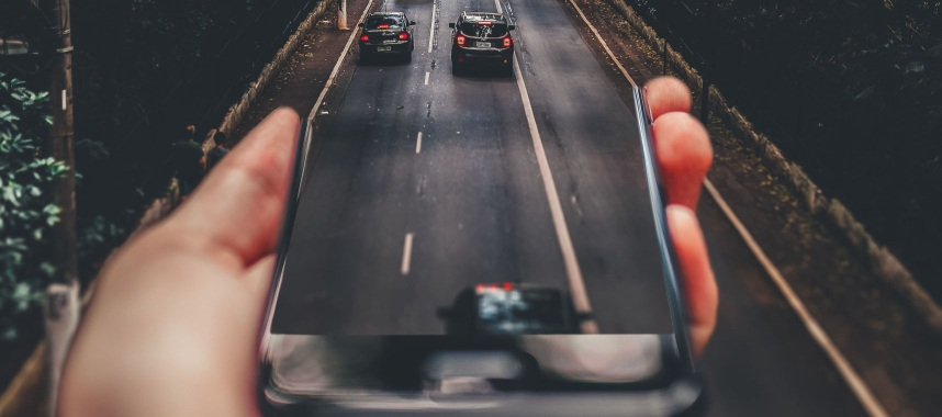 one of customer acquisition techniques this 2019 - outgoing cars to a a hand holding a phone-like road indicating correct timing in sending emails