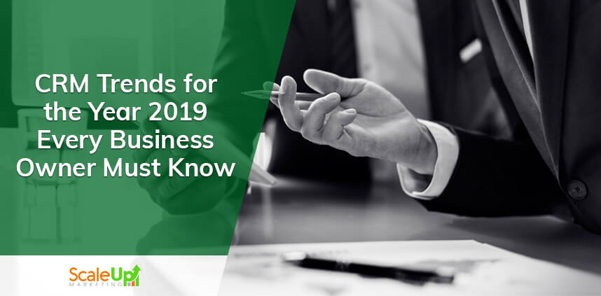 "ScaleUp Banner with a background Image of two men wearing black suit and a text ""CRM Trends for the Year 2019 Every Business Owner Must Know"""