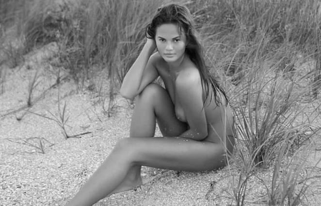 Chrissy Teigen sitting on the sand