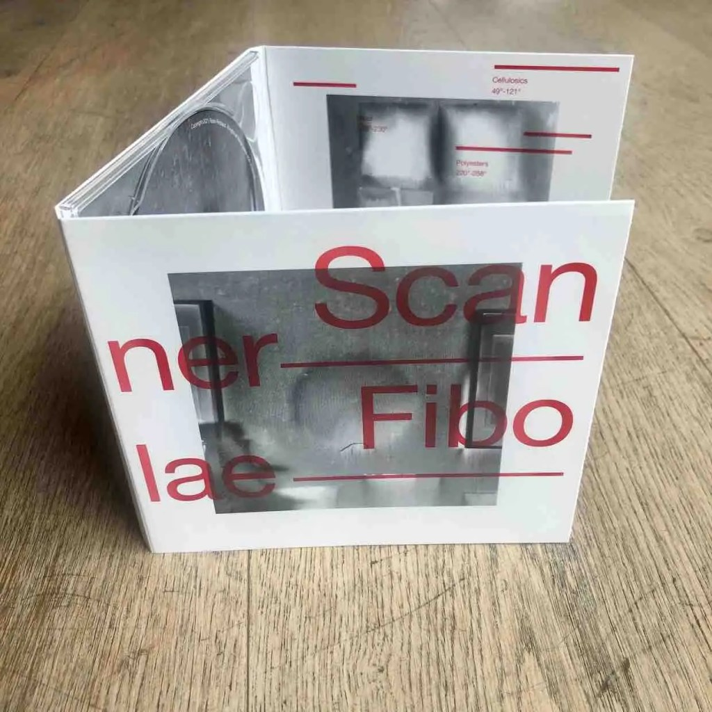 CD on a wooden floor, opened up. Black and white abstract images on the cover with a large text in red Scanner Fibolae on the front