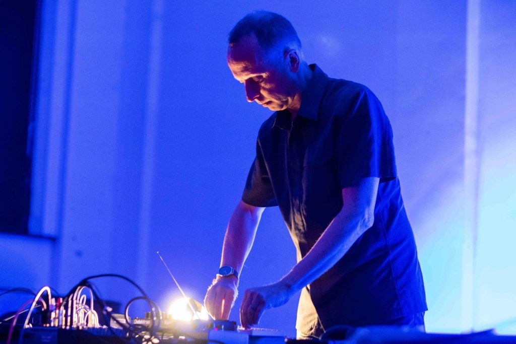 Man in black shirt playing electronic synthesiser, standing in front of table. Strong blue light all around to create drama