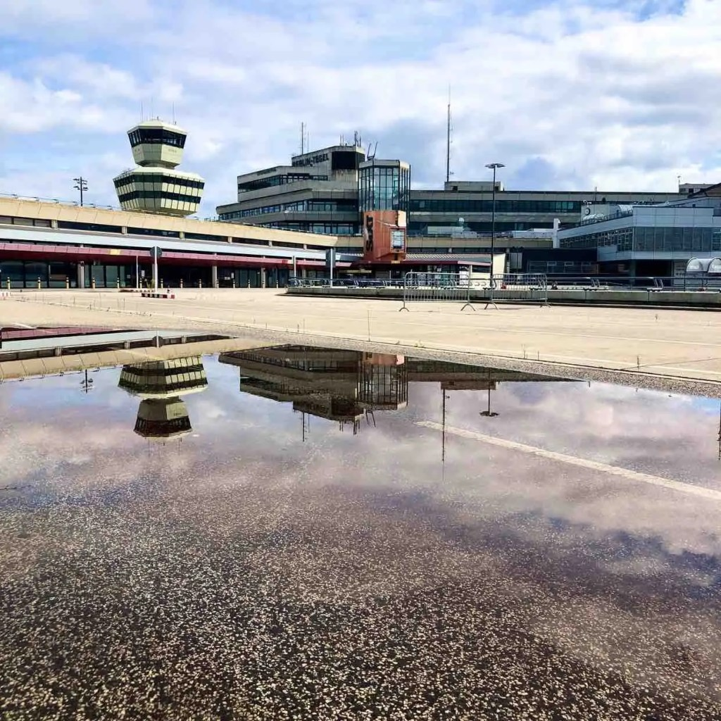 Colourful image of Tegel Airport in Berlin, devoid of people and travellers. You see a reflection of the building in a large rain puddle on the ground
