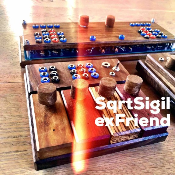 A very colourful image of three unusual looking wooden devices sit on the floor. A streak of light can be seen across the middle of the photo. The wooden devices each have wooden knobs on their surface and switches and buttons. Across the bottom of the image a text reads SqrtSigil exFriend