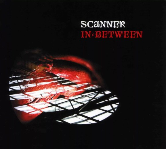 Artwork from a compact disc, with the artist and title IN BETWEEN written in a gothic script, above an image of a red heart set onto a black background