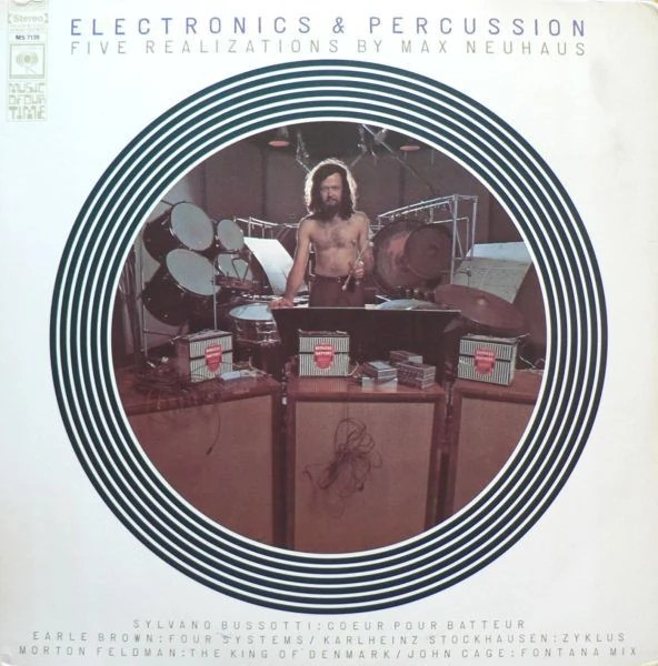 A vinyl LP record sleeved with a topless man, in brown trousers, standing in the centre of a giant circular image, surrounded by percussion equipment, holding a drum stick. Huge amplifiers stand at the front of the photo