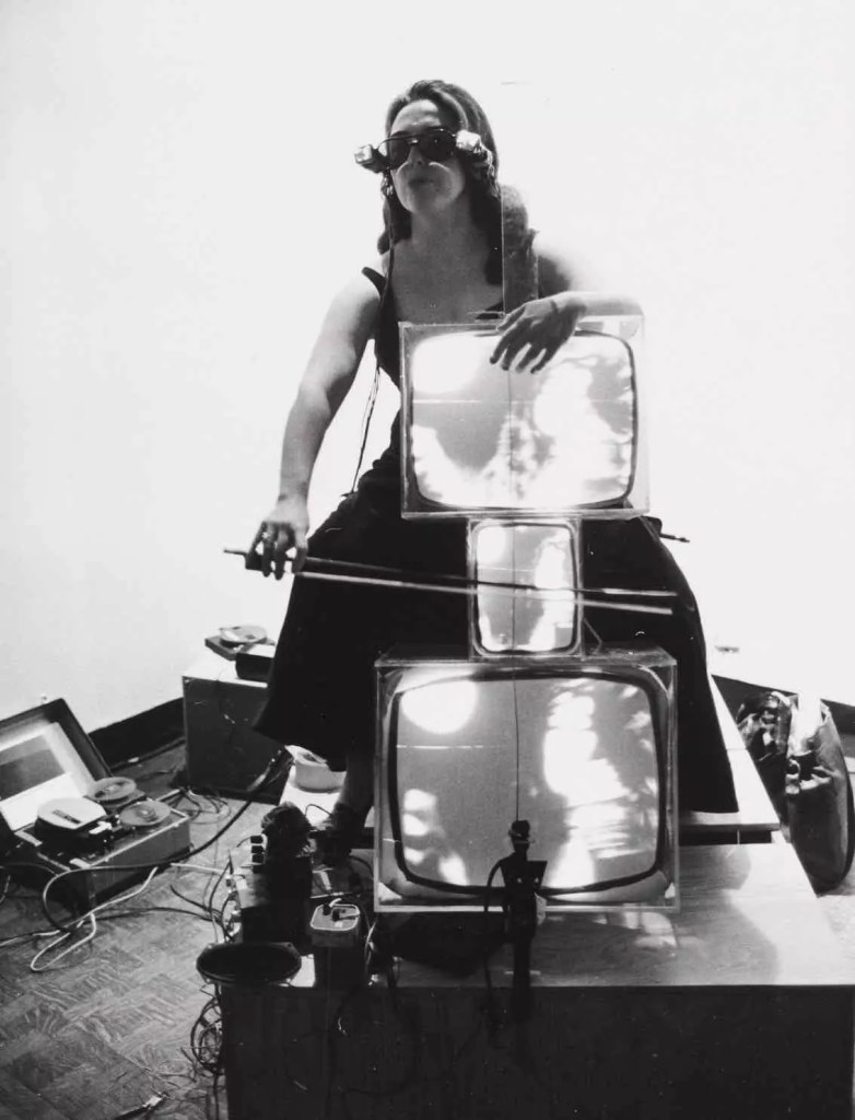 black and white image of a woman wearing glasses, sitting astride 3 television sets, old fashioned in style. She is holding a cello bow over the screens as if she is playing them. Wired and cables are all around her.