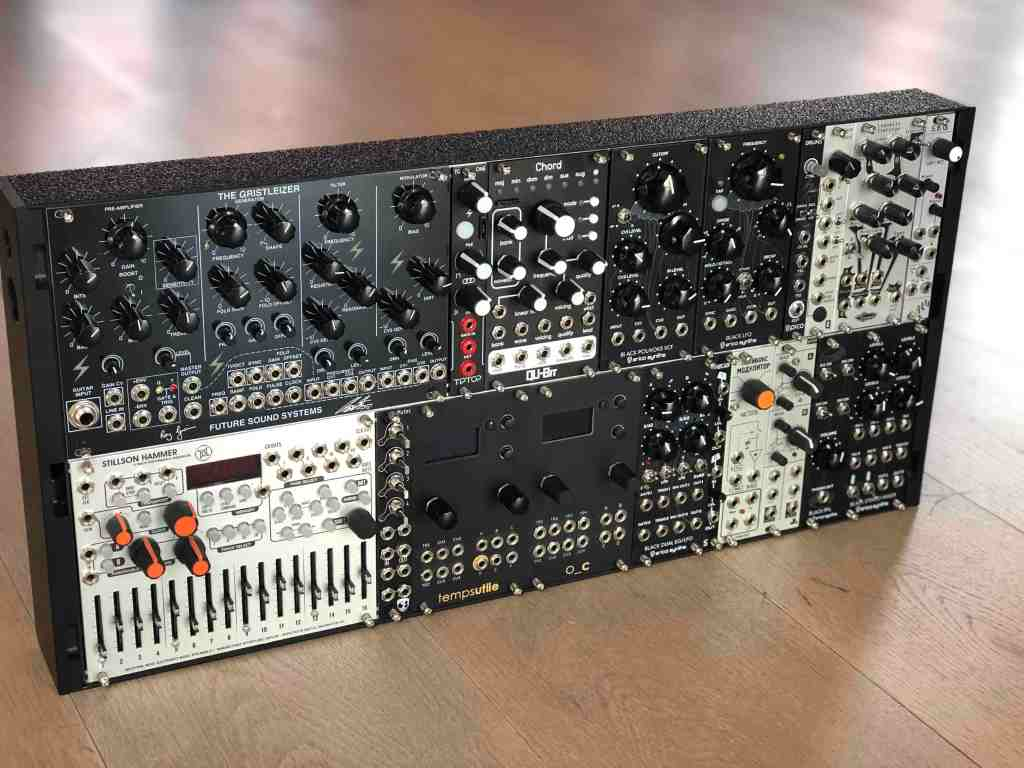 A black modular synth case standing upright on a wooden floor, filled with strange looking machines with buttons and knobs on them.