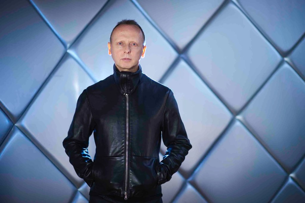 Image of man in his 50s, wearing a skinny leather jacket zipped up to his neck. Short crossed hair and staring directly at the camera, cool, no smile. Hands in pockets of jacket. Behind him is a shiny padded wall made of of angled squares, with light coming from behind him