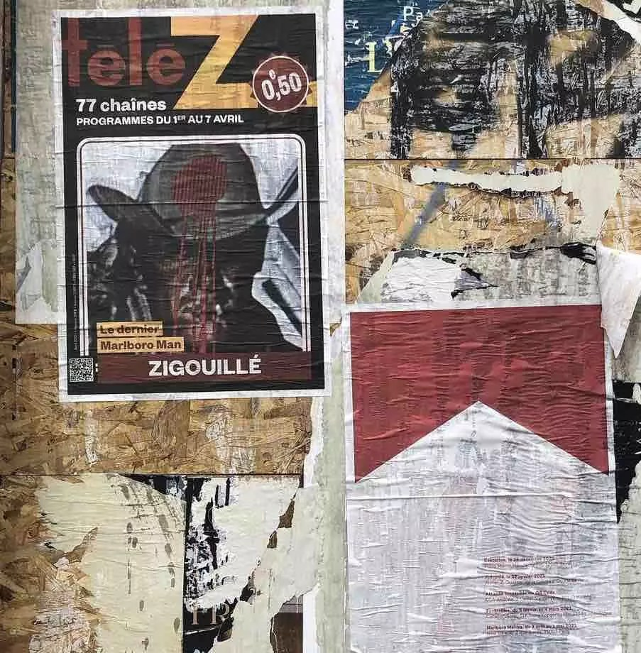 A wall in Paris covered in posters and graffiti. An image of the Marlboro Man with a bullet hole in his head is visible.