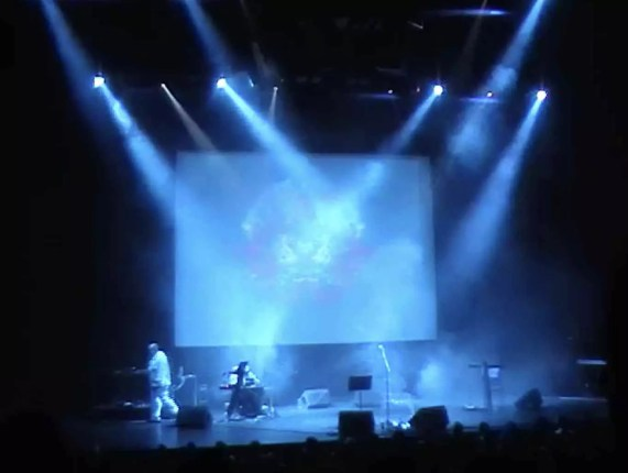 A blue black image of a stage in London, with a large projection screen with an abstract image on it and blue lights and smoke all around