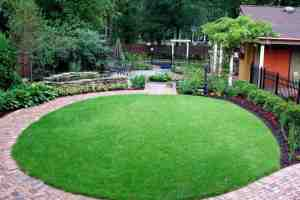 Lawn surrounded by brick path and landscaping