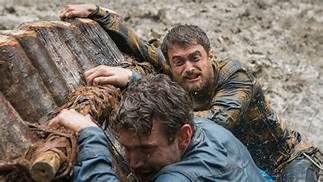 Yossi (Daniel Radcliffe) and Kevin (Alex Russell) hang on for dear life to their makeshift wooden raft in Jungle.
