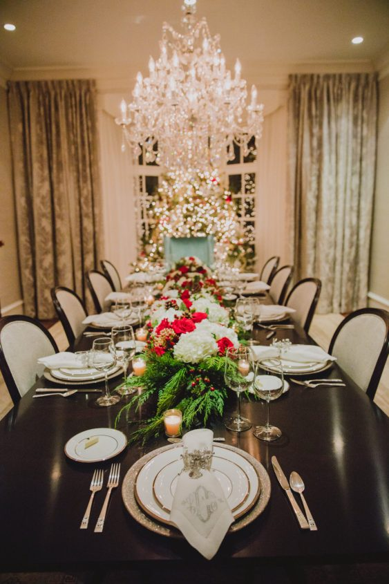 formal glam Christmas tablescape feauturing traditional greenery and red and white florals